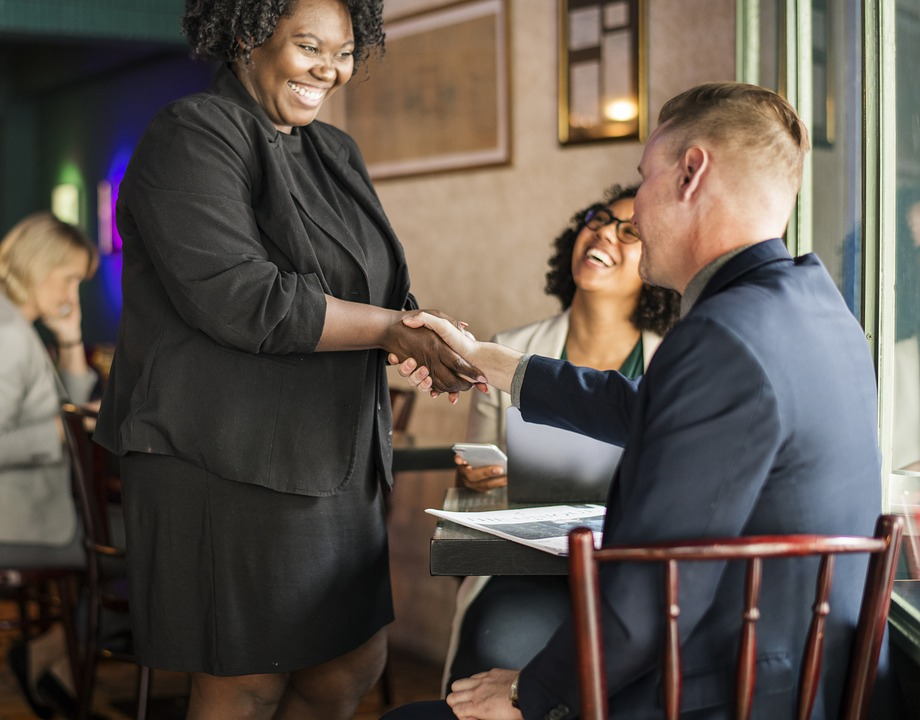 smiling woman shaking hands with seated man